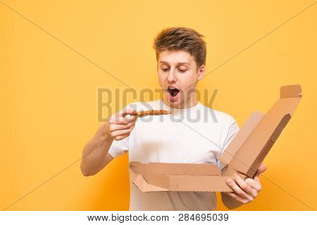 Hungry Guy With Pizza In His Hands Is Isolated On A Yellow Background. Emotional Young Man In A Whit