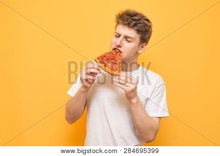 Guy In A White T-shirt Eats An Appetizing Piece Of Pizza With His Eyes Closed On A Yellow Background
