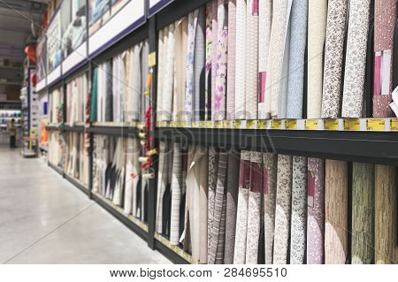 Many Different Colored Wallpapers In The Supermarket Showcase. Choice Of Wallpapers In A Warehouse.