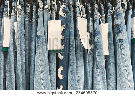 Blurred Background With Jeans. Background Jeans In A Clothing Store, New Jeans With Prices And Tags