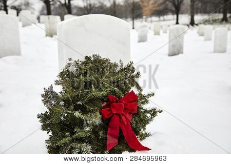 Headstone in a cemetery with a wreath made out of pine branches in the winter with snow on the ground poster