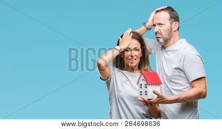 Middle age hispanic casual couple buying new house over isolated background stressed with hand on head, shocked with shame and surprise face, angry and frustrated. Fear and upset for mistake.