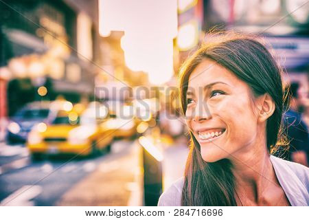 Happy people New York city lifestyle young Asian woman smiling in sunset walking in street with taxi cabs traffic sun shining down in downtown Manhattan, New York City.