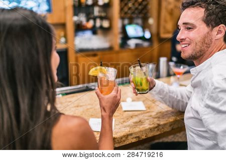 Cocktails drinking couple at lobby bar toasting drinks talking with at restaurant date night. People at restaurant with alcoholic cocktail glass. Man looking at woman.