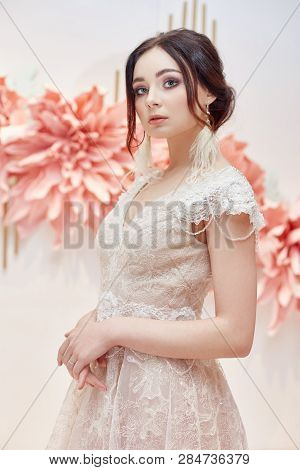 Luxury Woman Bride In A Beautiful Expensive Wedding Dress On The Background Of Large Artificial Flow