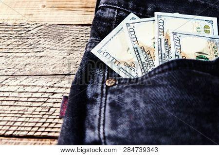 Dollar Bills In The Back Pocket Of Jeans