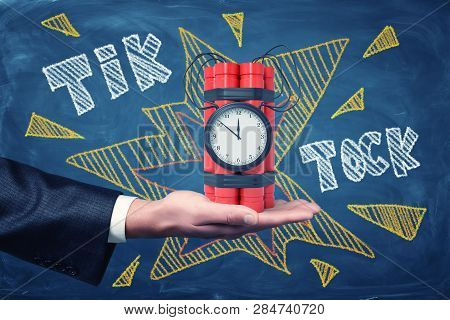 Mans Hand Facing Up Holding Dynamite Bundle With Time Bomb On Blackboard Background With Chalk Words