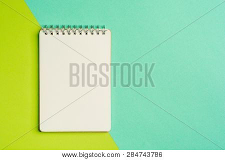 Top View Of Spiral Notepad On Colored Surface. Flat Lay Style With Place For Text. Trendy Color Conc