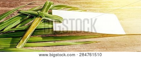 Closeup View Of Cross Shape Of Palm Leaf And Palm Branches With White Blank Paper And Ray In Wooden