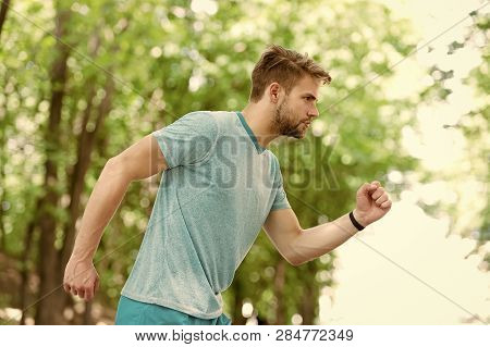 Moving To His Goal. Man Confident Young Running In Park, Side View. Sportsman Ambitiously Moves To A