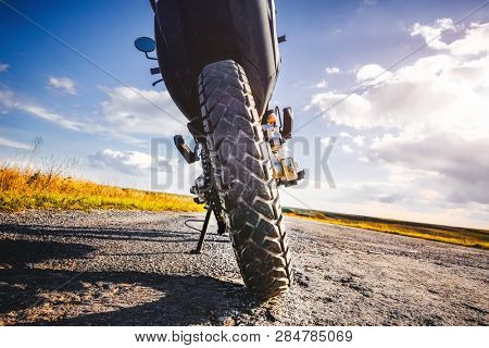 Studded cross motorcycle wheel on the ground level. Focus on the rear wheel. Details of a motorbike closeup. Traveling concept. Driving the empty road on a tour journey. Discover the beauty of earth.