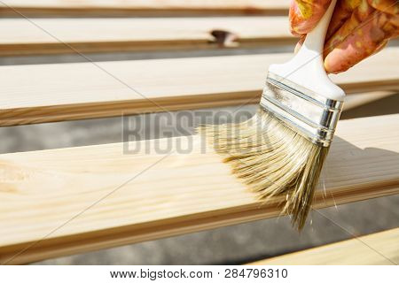 Painter Holding A Paintbrush Over Wooden Surface, Protecting Wood For Exterior Influences And Weathe