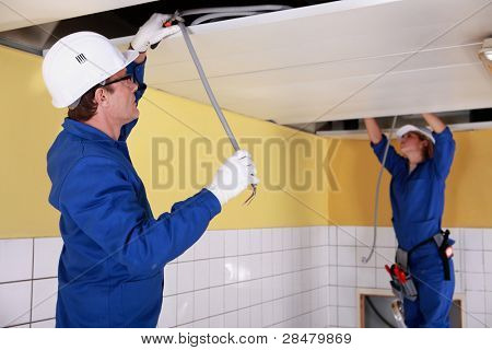 Two electricians repairing ceiling wiring