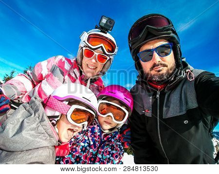 Family Enjoying Winter Vacations Taking Selfie In Skiing Gear. Family With Children On Skiing Vacati