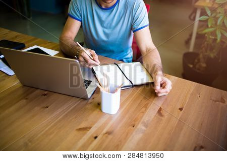 Writer Writing Information In Notepad Sitting At Wooden Table With Laptop Computer In Coworking Spac