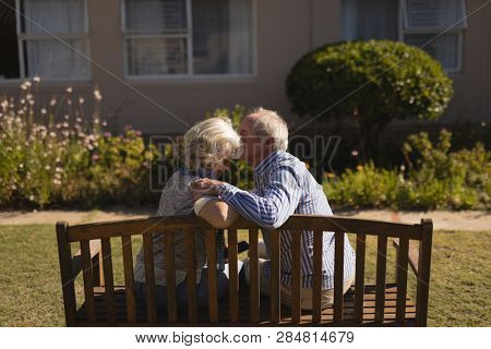 Rear view of active senior Caucasian man kissing senior Caucasian woman in the park