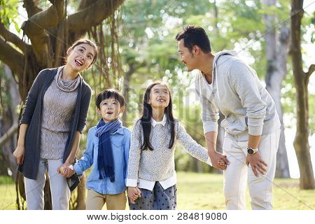 Asian Family With Two Children Having Fun Exploring Woods In A Park.
