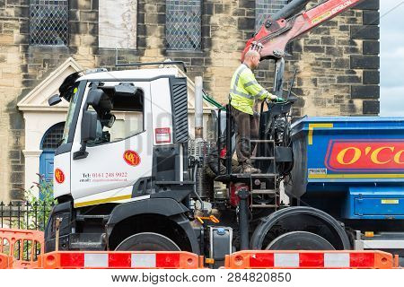 Wrexham, Uk - August 25, 2017: Roadworks. Close Up Of Workman Standing On Truck Behind Cab Operating