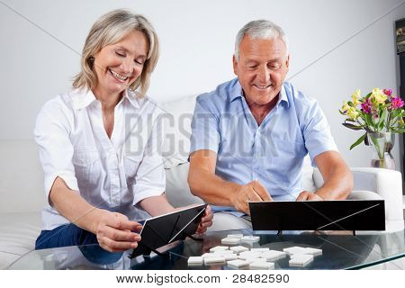 Happy senior couple playing rummy together at home.