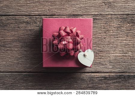 Red Gift Box With Mini Heart Shape On Old Wooden Background, Valentines Day Concept