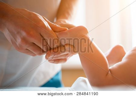 Masseur does foot massage for small child lying on stomach.