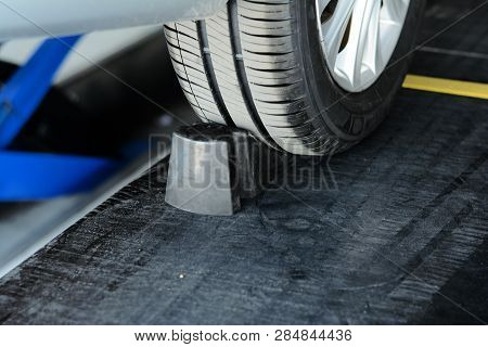 Metal Wheel With Black Tyre On Alignment Podium At Car Repair Shop