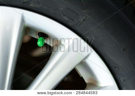 The Green Cover Of Tyre Pressure Valve On Metal Wheel With   Black Tyre