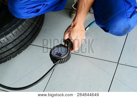 The Mechanic In Blue Uniform Fill Up The Air Into The Metal Wheel And Black Tyre