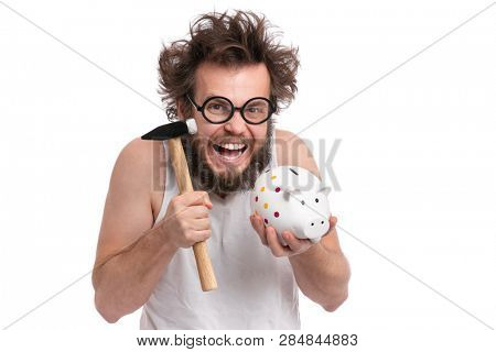 Crazy bearded Man with funny Haircut in eye Glasses holding Piggy Bank and Hammer, isolated on white background. Saving Money concept. Male about to break  piggybank.