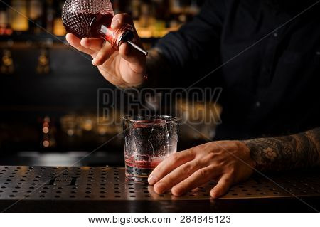 Bartender Adding A Bitter To The Cocktail From The Special Dasher Bottle On The Bar Counter On The B
