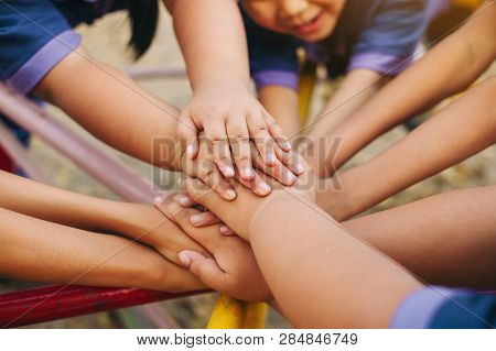 Group Of Diverse Kids Hands Of Together Joining For Teamwork, Community,  Togetherness And Collabora
