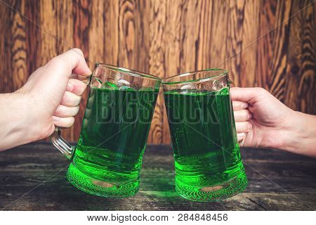 St Patrick's Day Concept. Friends Toast With Glasses Of Green Beer At The Pub. Friends Celebrate St.