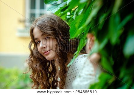 Portrait Of A Young, Sympathetic, Dark-haired Woman In A Park Near The House.