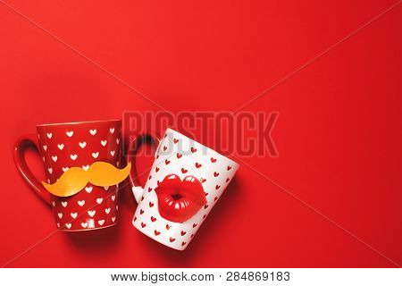 Couple Of Red Cup With Mustache And White Cup With Lips Painted With Hearts On Vibrant Background. V