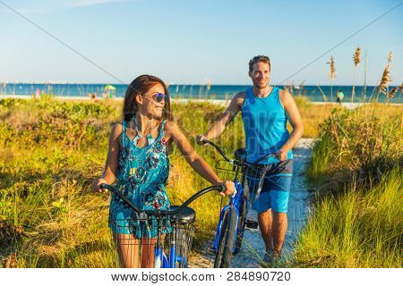 Summer people lifestyle happy couple biking on beach relaxing outdoors activity at sunset. Young woman and man riding leisure bicycles on USA Florida holidays getaway.