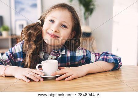 Happy Kid Girl Drinking Tea For Breakfast. Indoor Portrait Of 9 Years Old Child