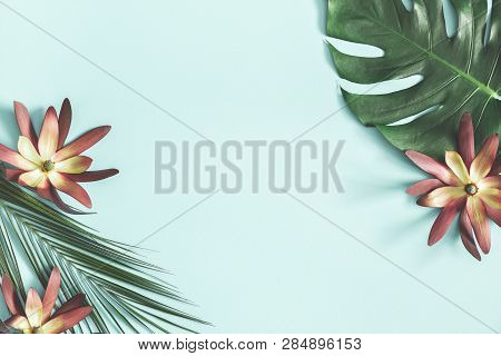 Summer Composition. Tropical Flowers And Leaves On Pastel Blue Background. Summer Concept. Flat Lay,