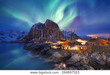 Aurora Borealis On The Lofoten Islands, Norway. Green Northern Lights Above Ocean. Night Sky With Po