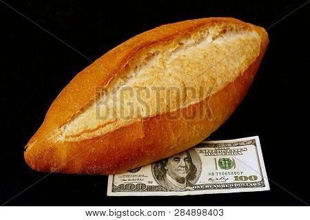 Bread And $ 100 Dollars, Fresh Baked Whole One Bread And Next To 100 Usd Dollar, Close Up,