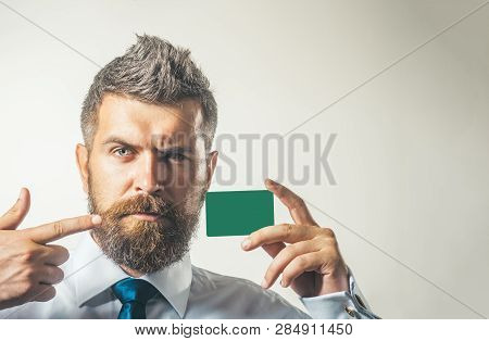 Serious Business Man Holds Credit Card Pointing On It. Handsome Man In White Shirt With Credit Card.