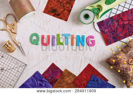 Wooden Letters, Consisting To The Word Quilting Surrounded By Accessories For Quilting