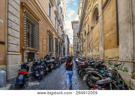 Rome, Italy - September 29 2018: A Woman Walks Alone Down A Narrow Side Street With Many Motorcycles