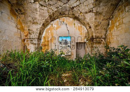 View Through A Window In A Medieval, Cracked Stone Wall Of The Ancient Madonna De Idris Rock Church