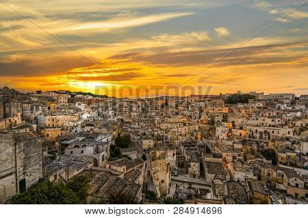 A Colorful Sunset Over The Ancient City Of Matera Italy, As The Lights Come On And Illuminate The Ch