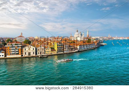 Venice, Italy - September 18 2018: A Water Taxi Cruises The Grand Canal With The Dome Of Santa Maria