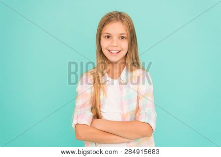 Kid Girl Blonde Hair Posing Confidently. Girl Feels Confident With Crossed Arms. Child Hold Hands Co