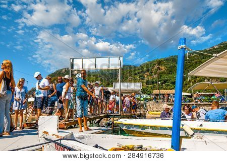 Corfu, Greece - September 20 2018: A Tour Boat Leader Maintains The Boats In The Dock As Tourists Li