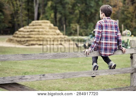 Boy Sitting On The Fence. Kid Having Fun At Farm. Copy Space For Your Text