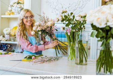 Beautiful Happy Female Florist In Glasses Arranging Bouquet In Flower Shop