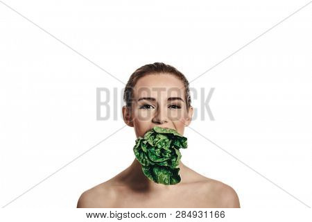 Vegan diet. Woman with lettuce in mouth isolated on white background.